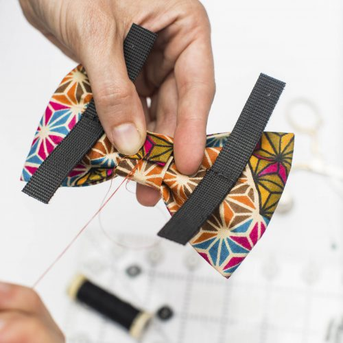 Dog bow attaches to collars with hook and loop tape.