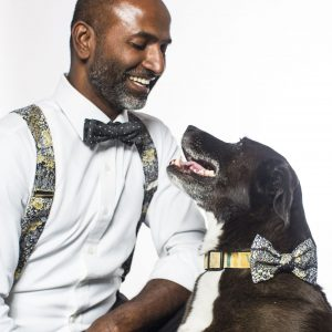 Titus and his dog sporting matching black flowers suspenders and dog bow.
